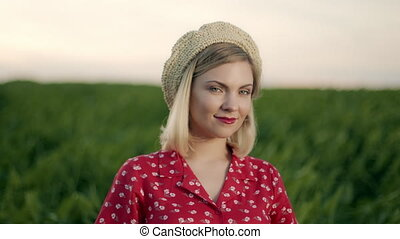 Beautiful portrait of attractive blonde woman in straw beret hat on green nature background. Retro floral dress, red lips. Pleasant feminine appearance, kind smile. 4k slow motion.