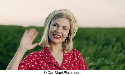 Beautiful portrait of attractive blonde woman waving hand, smiling, greeting. Lady in straw beret hat on green nature background. Pleasant feminine appearance, kind smile. 4k slow motion.