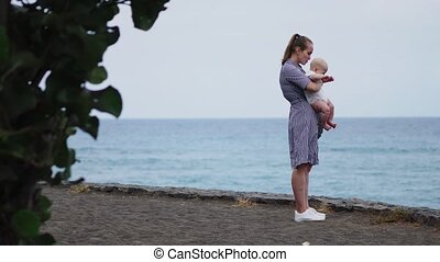 Beautiful portrait of mother kiss daughter on the sea and beach background. Happy family in vacation. Travel. Mom hugs toddler on sunset. Caucasian female with baby outside at ocean. Motherhood care.