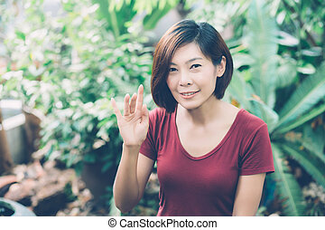 Beautiful portrait young asian woman smiling waving hand in garden at home, Friendly girl and expression positive of emotion, hello and greeting, one person, happy female excited and cheerful.