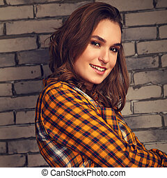 Beautiful positive toothy smiling woman looking happy in casual orange cell shirt on brick blue studio background.