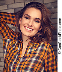 Beautiful positive toothy smiling woman looking happy in casual orange cell shirt on brick blue studio background. Closeup