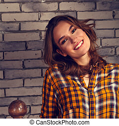 Beautiful positive toothy smiling woman looking happy in casual orange shirt and blue jeans