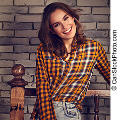 Beautiful positive toothy smiling woman looking happy in casual orange shirt and blue jeans on brick studio background. Toned
