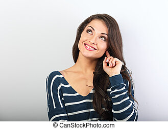 Beautiful positive young casual woman in warm sweater thinking and looking up on blue background with empty copy space