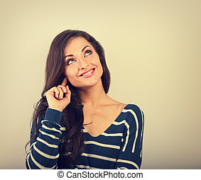 Beautiful positive young casual woman in warm sweater thinking and looking up on empty copy space. background. Toned vintage portrait
