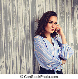 Beautiful positive young happy woman with hand under the face thinking and looking in casual blue shirt
