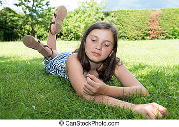 Beautiful pre teenage girl laying in grass