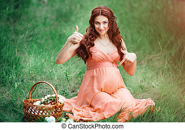 Beautiful pregnancy concept. Brunette happy woman sitting on grass with curly hair on nature background.