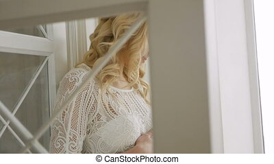 beautiful pregnant blonde girl in white knitted dress...