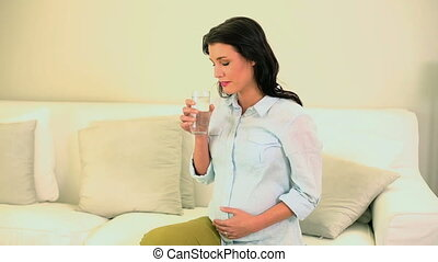 Beautiful pregnant brunette drinking water