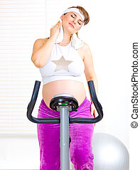 Beautiful pregnant female wiping her face with towel after training on static bicycle
