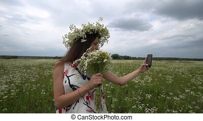Beautiful pregnant girl doing selfie, photo with camomile flowers outside.
