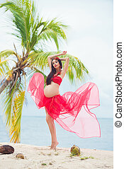 Beautiful pregnant girl in red dress on sandy beach with palm trees