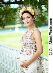 Beautiful pregnant girl with a wreath of flowers