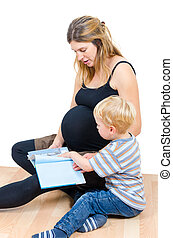 Beautiful pregnant happy mother with child boy reading a book isolated on white background