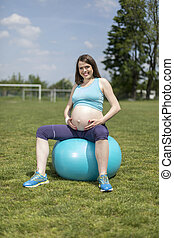 Beautiful pregnant woman at fitness gym relaxed