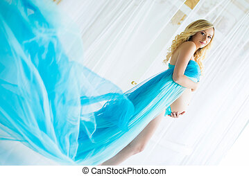 Beautiful pregnant woman. Attractive blonde touching naked...