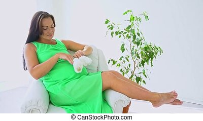 Beautiful Pregnant woman caressing her belly. Woman touching...