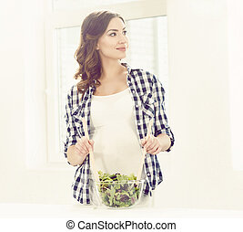 Beautiful pregnant woman cooking in the kitchen