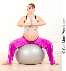 Beautiful pregnant woman doing pilates exercises on gray ball