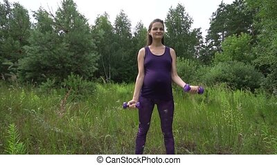 Beautiful pregnant woman doing sport in summer park.