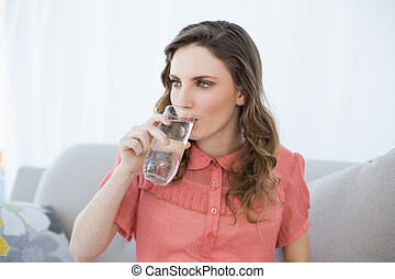 Beautiful pregnant woman drinking glass of water sitting on couch in living room at home