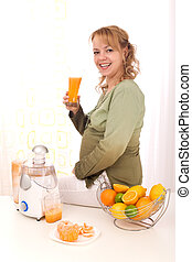 Beautiful pregnant woman drinking orange juice