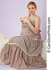 Beautiful pregnant woman drinking t