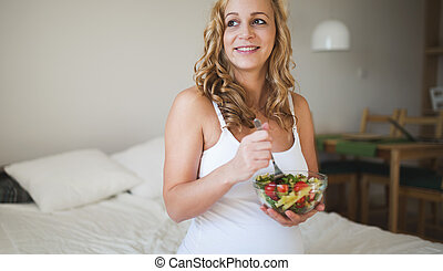 Beautiful pregnant woman eating healthy food