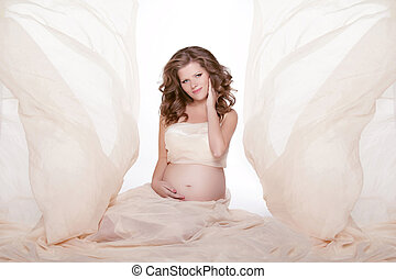 Beautiful pregnant woman expecting a baby and stroking her belly isolated on white background. Studio Photo