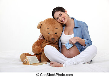 beautiful pregnant woman holding a teddy bear