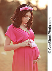 Beautiful pregnant woman holding baby's bootee over nature park background at sunset. Roses flower in hand of pretty female.