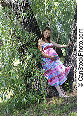 Beautiful pregnant woman in a city park.