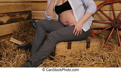 Beautiful pregnant woman in a shirt and a cowboy hat.