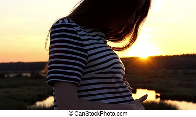 Beautiful pregnant woman in a striped dress is on a lake bank at sunset
