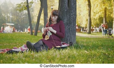 Beautiful pregnant woman in autumn park make hobby knitting needles