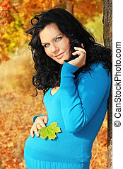 Beautiful pregnant woman in blue jacket relaxing in the autumn park