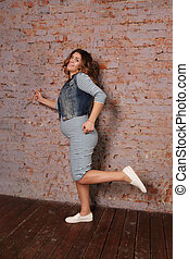 beautiful pregnant woman in striped dress, jacket is running near brick wall in studio
