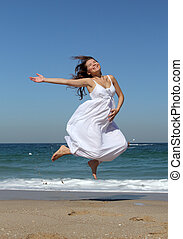 beautiful pregnant woman jumping on the beach