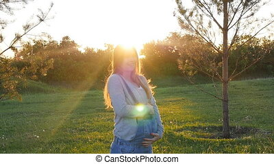 Beautiful pregnant woman on grass