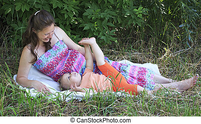 Beautiful pregnant woman playing with her ??little daughter