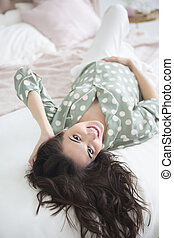 Beautiful pregnant woman posing while lying on a bed at home