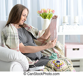 beautiful pregnant woman sitting in armchair