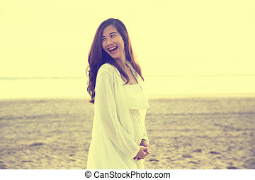 Beautiful pregnant woman smile brightly in white dress on the beach