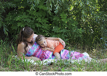 Beautiful pregnant woman tenderly deals with a little daughter.