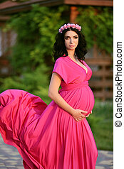 Beautiful pregnant woman touching her belly wearing in pink dress and flowers chaplet, resting in summer park at sunset.