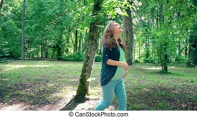 beautiful pregnant woman walking in park on sunny summer...