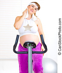 Beautiful pregnant woman wiping her face with towel after training on static bicycle