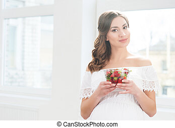 Beautiful pregnant woman with a bowl of strawberries.